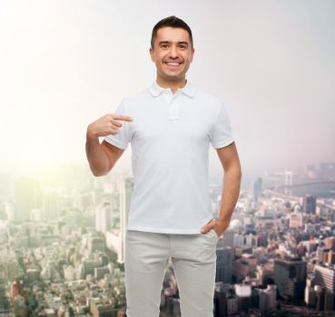 happiness, advertisement, fashion, gesture and people concept - smiling man in t-shirt pointing finger on himself over city background