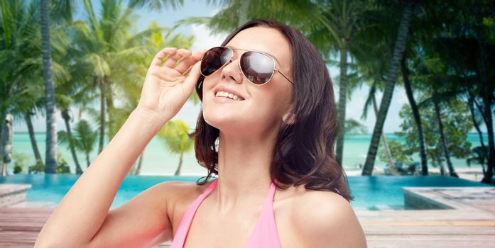 people, travel, tourism and summer resort concept - happy young woman in sunglasses looking up over swimming pool and beach with palm trees background