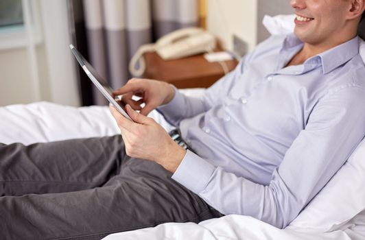 business trip, technology, internet and people concept - smiling businessman with tablet pc computer lying on bed at hotel room