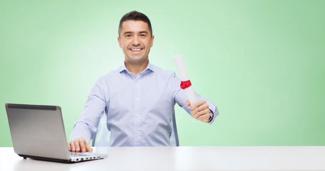 education, graduation, business, technology and people concept - smiling man with diploma and laptop computer sitting at table over green background