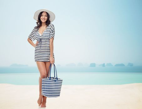 people, fashion, summer and beach concept - happy young woman in summer clothes and sun hat with bag over infinity pool at beach resort