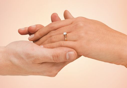 jewelry, couple, love and wedding concept - close up of man and woman hands with engagement ring over beige background