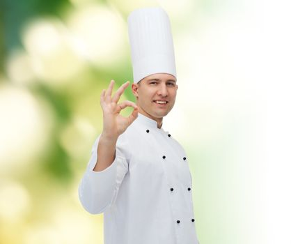 cooking, profession, gesture and people concept - happy male chef cook showing ok sign over green background