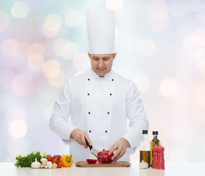 cooking, profession, vegetarian, food and people concept - happy male chef chopping pepper over blue lights background