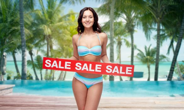 people, summer, travel and tourism concept - happy young woman in bikini swimsuit with red sale sign over swimming pool and beach with palm trees background