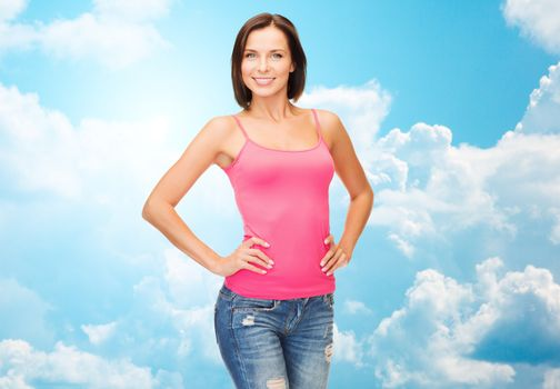 people, advertisement and clothing concept - smiling woman in blank pink tank top over blue sky with white clouds background