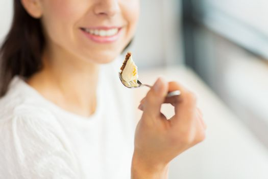 food, dessert, people and lifestyle concept - close up of smiling young woman holding fork and eating cake at cafe or home
