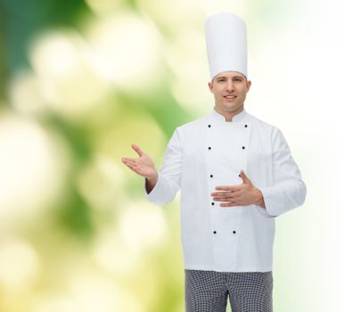 cooking, profession and people concept - happy male chef cook inviting over green background