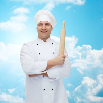 cooking, profession and people concept - happy male chef cook holding rolling pin over blue sky with clouds background