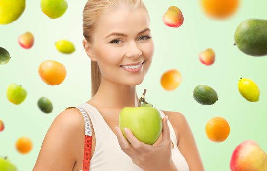 healthy eating, diet, slimming, weight control and people concept - happy young sporty woman with apple and measuring tape over green background with falling fruits