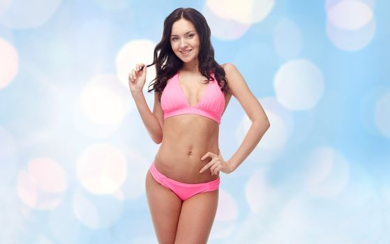 people, swimwear, summer beach and sexual concept - happy young woman posing in pink bikini swimsuit over blue holidays lights background