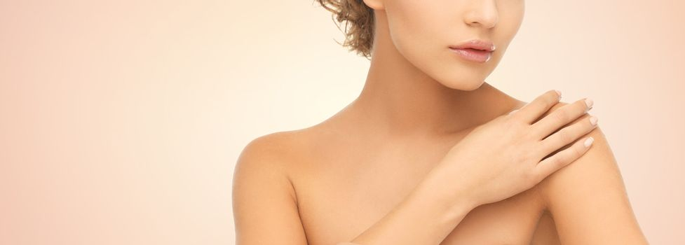 beauty, people and health concept - close up of beautiful young woman with bare shoulders over beige background