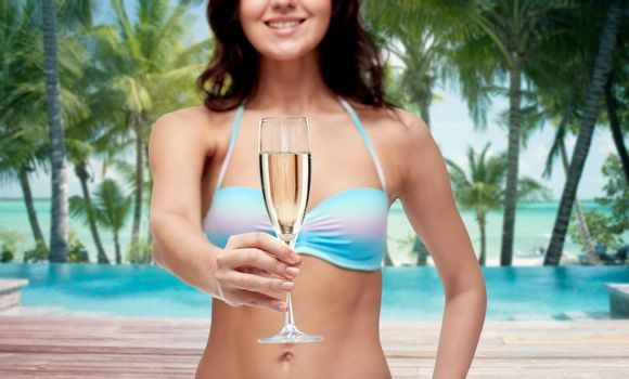 people, travel, tourism, summer holiday and celebration concept - happy young woman in bikini swimsuit drinking champagne at party over swimming pool and beach with palm trees background