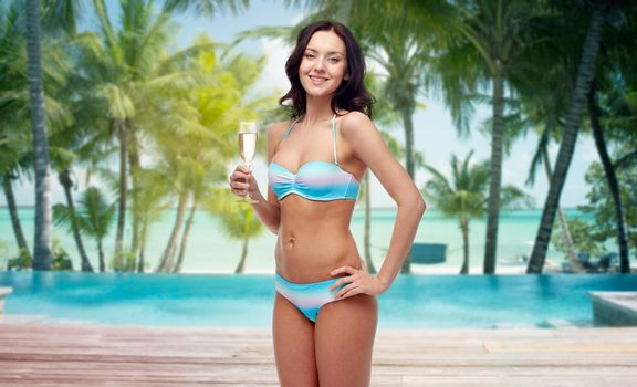 people, travel, tourism, summer holidays and celebration concept - happy young woman in bikini swimsuit drinking champagne at party over swimming pool and beach with palm trees background