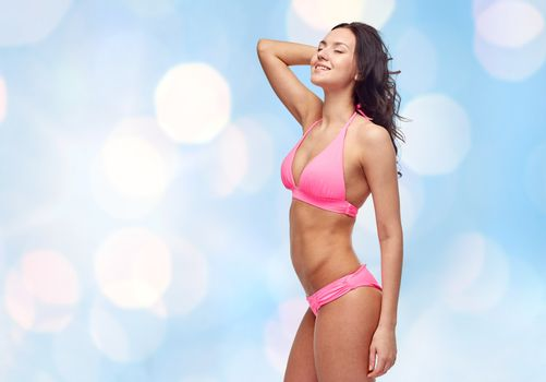 people, fashion, swimwear, summer and beach concept - happy young woman posing in pink bikini swimsuit over blue holidays lights background