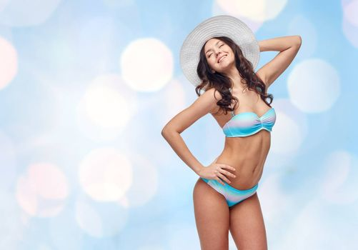 people, fashion, swimwear, summer and beach concept - happy young woman in bikini swimsuit and sun hat over blue holidays lights background
