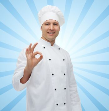 cooking, profession, gesture and people concept - happy male chef cook showing ok sign over blue burst rays background