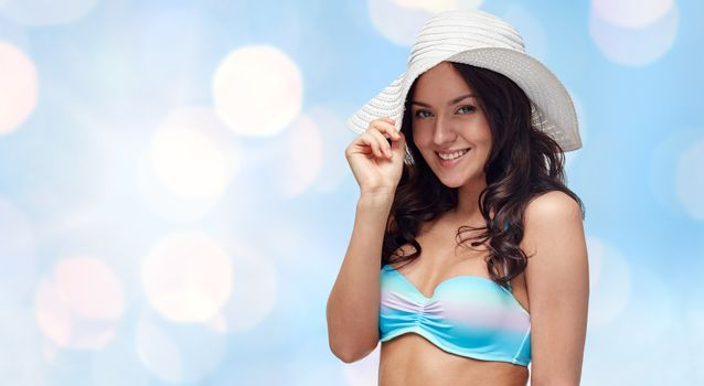 people, fashion, summer and beach concept - happy young woman in bikini swimsuit and sun hat over blue holidays lights background