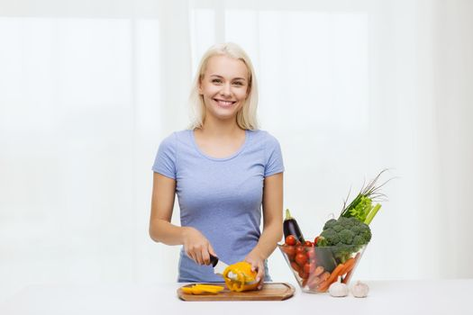healthy eating, vegetarian food, cooking, dieting and people concept - smiling young woman chopping vegetables at home