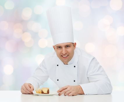 cooking, profession, haute cuisine, food and people concept - happy male chef cook with dessert over blue lights background