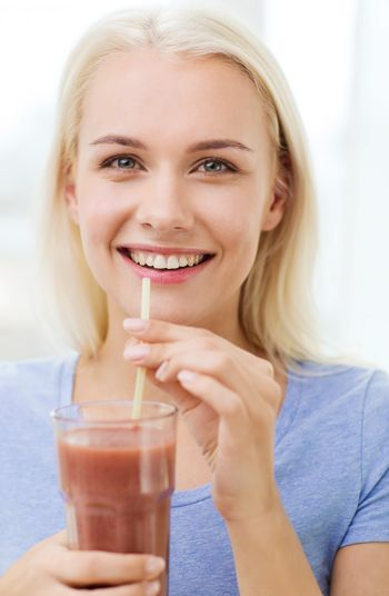 healthy eating, vegetarian food, dieting and people concept - smiling woman drinking juice or shake from glass at home