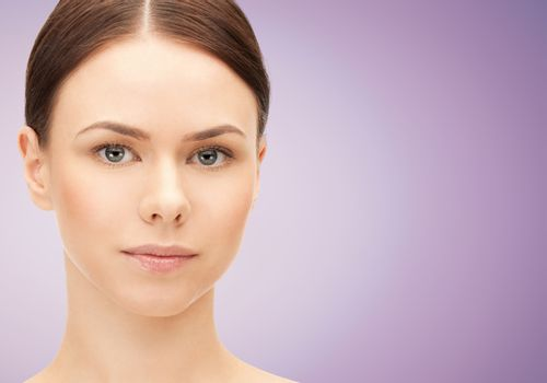 health, people and beauty concept - beautiful young woman face over violet background