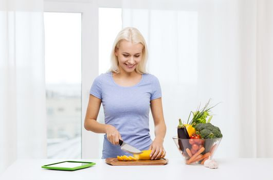healthy eating, vegetarian food, dieting and people concept - smiling young woman cooking vegetables with tablet pc computer at home