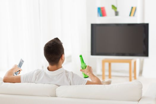 leisure, technology, mass media and people concept - man watching tv and drinking bottle beer at home from back