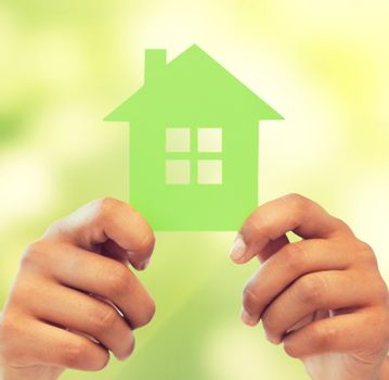business, eco and real estate concept - closeup picture of woman hands holding green house
