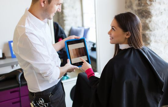 beauty, technology and people concept - happy young woman and stylist with tablet pc computer choosing hair color at salon