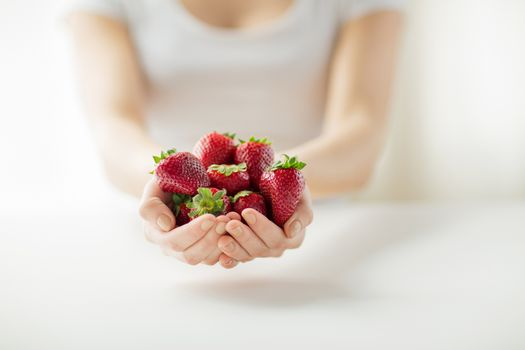 healthy eating, dieting, vegetarian food and people concept - close up of woman hands holding strawberries at home