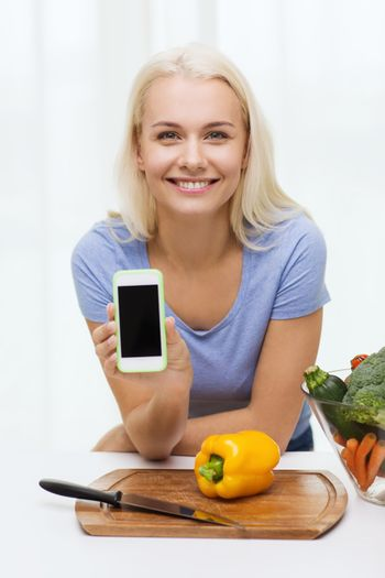 healthy eating, vegetarian food, dieting and people concept - smiling young woman cooking vegetables and showing blank smartphone screen at home
