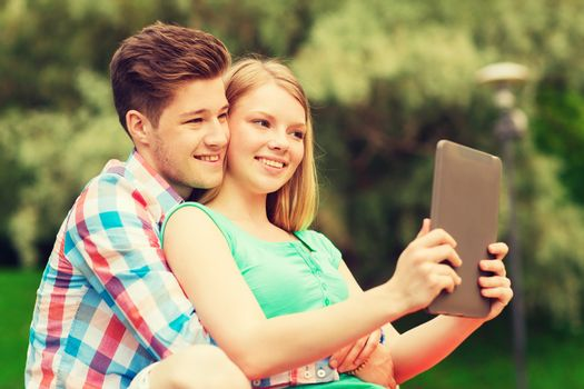 vacation, holidays, technology and friendship concept - smiling couple with tablet pc computer making selfie in park