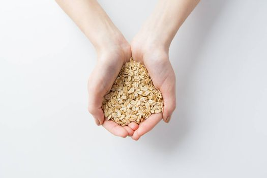 healthy eating, dieting, vegetarian food and people concept - close up of woman hands holding oatmeal flakes at home