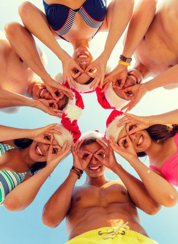 friendship, christmas, summer vacation, holidays and people concept - group of smiling friends wearing swimwear and santa helper hats standing and having fun in circle over blue sky
