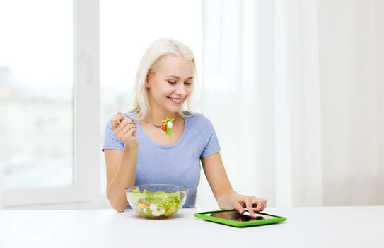 healthy eating, dieting and people concept - smiling young woman with tablet pc computer eating vegetable salad at home