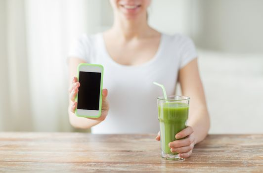 healthy eating, diet, detox, technology and people concept - close up of woman with smartphone green juice sitting at wooden table