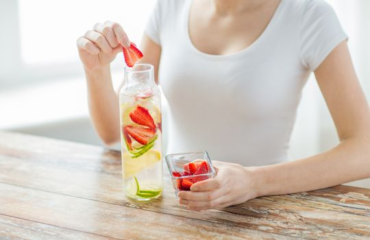 healthy eating, drinks, diet, detox and people concept - close up of woman with fruit water in glass bottle