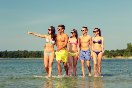 friendship, summer vacation, sea, gesture and people concept - group of smiling friends wearing swimwear and sunglasses walking and pointing finger on beach