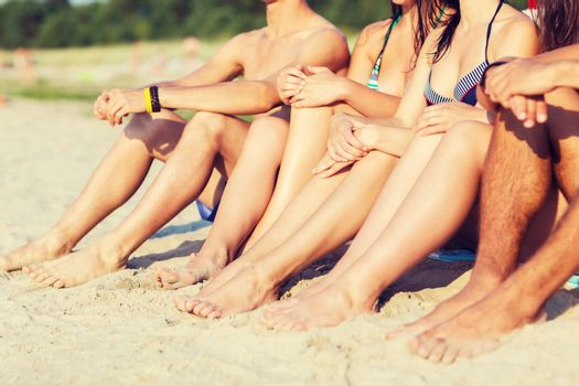 friendship, happiness, summer vacation, holidays and people concept - close up of friends sitting beach
