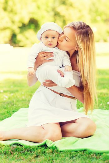 family, child and parenthood concept - happy mother kissing her little baby and sitting on blanket in park