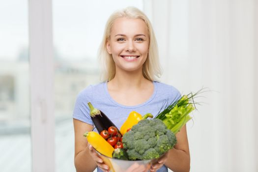 healthy eating, vegetarian food, dieting and people concept - smiling young woman with bowl of vegetables at home