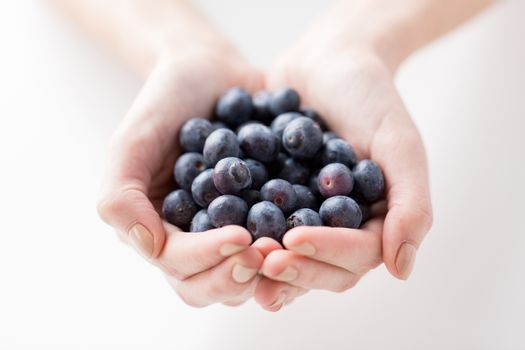 healthy eating, dieting, vegetarian food and people concept - close up of woman hands holding blueberries at home