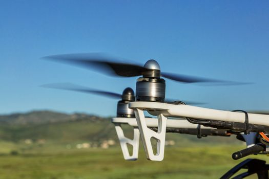 blurred spinning propellers of a hexacopter drone flying over foothills prairie