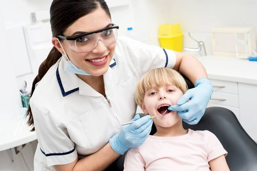Dentist examining a little girl patient
