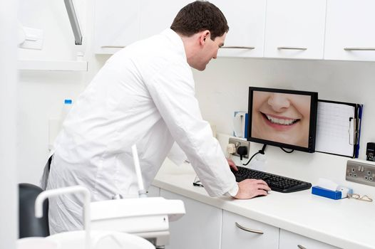 Dentist checking patient teeth in computer screen