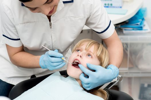 Cute kid undergoing dental treatment at clinic