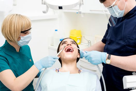 Male dentist treating patient teeth with assistant