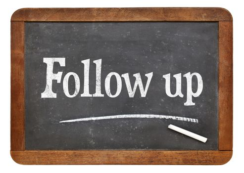 Follow up sign- text in white chalk on a vintage slate blackboard