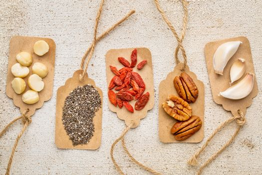 superfood abstract with price tags against  rustic barn wood (macadamia and pecan nuts, goji berries, chia seeds and garlic cloves) - healthy eating concept